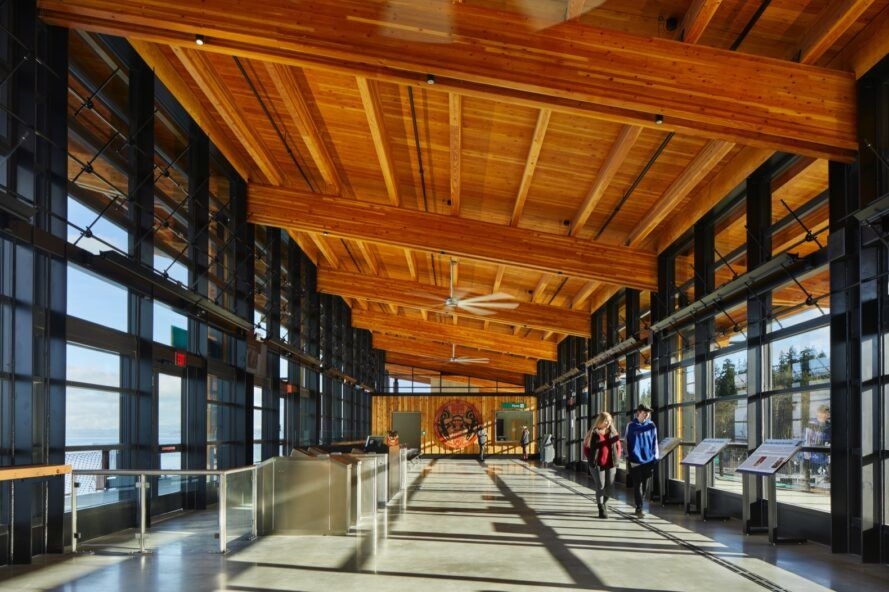 people walking through transit hub with wood ceiling and glass walls