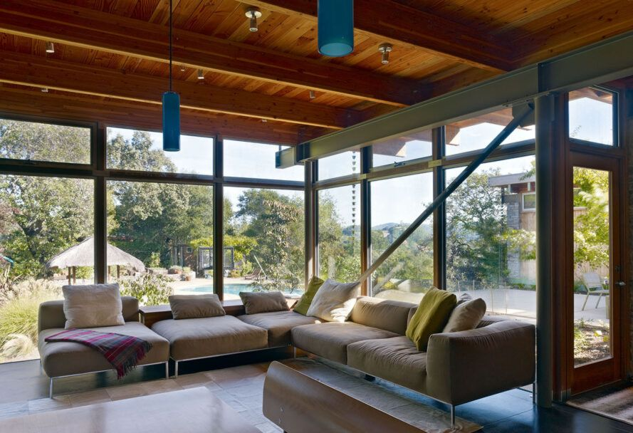 A living room with a beige L-shaped sofa. Behind the sofa, floor-to-ceiling windows look out on the backyard.