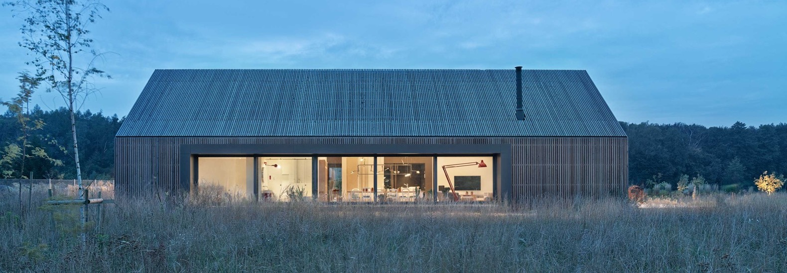 Modern, barn-inspired home ages gracefully in a wild Poznań meadow