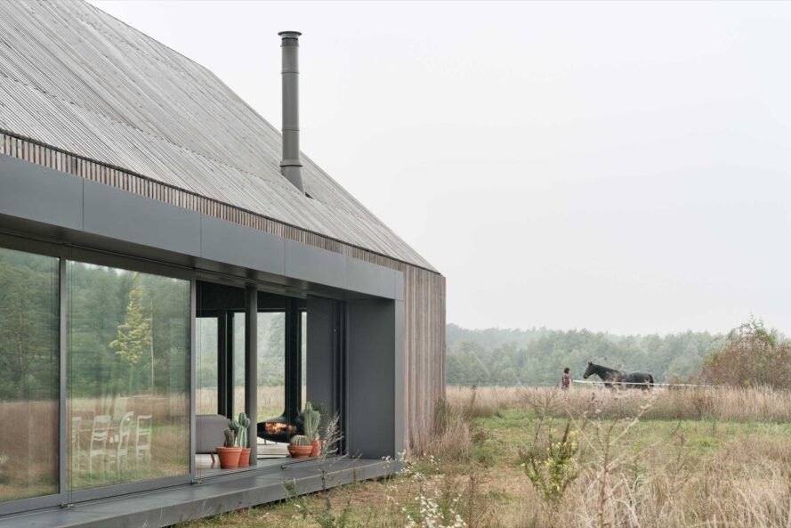 wood home with glass wall facing a meadow