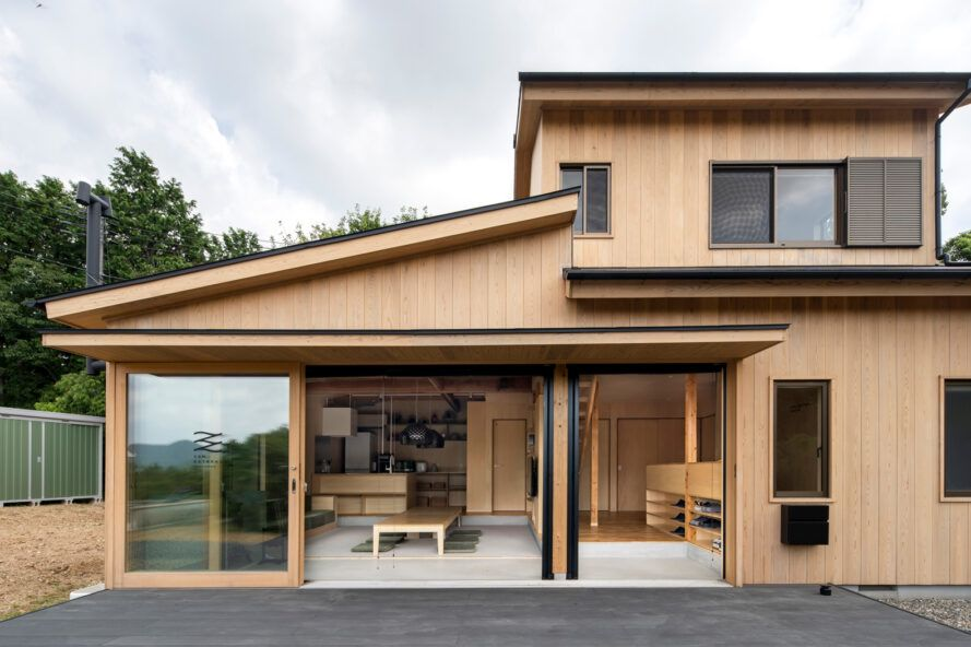 cedar building with glass wall open to outdoor patio