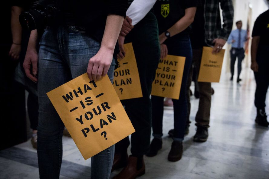 """A line of activists holding signs saying """"What is your plan?"""""""