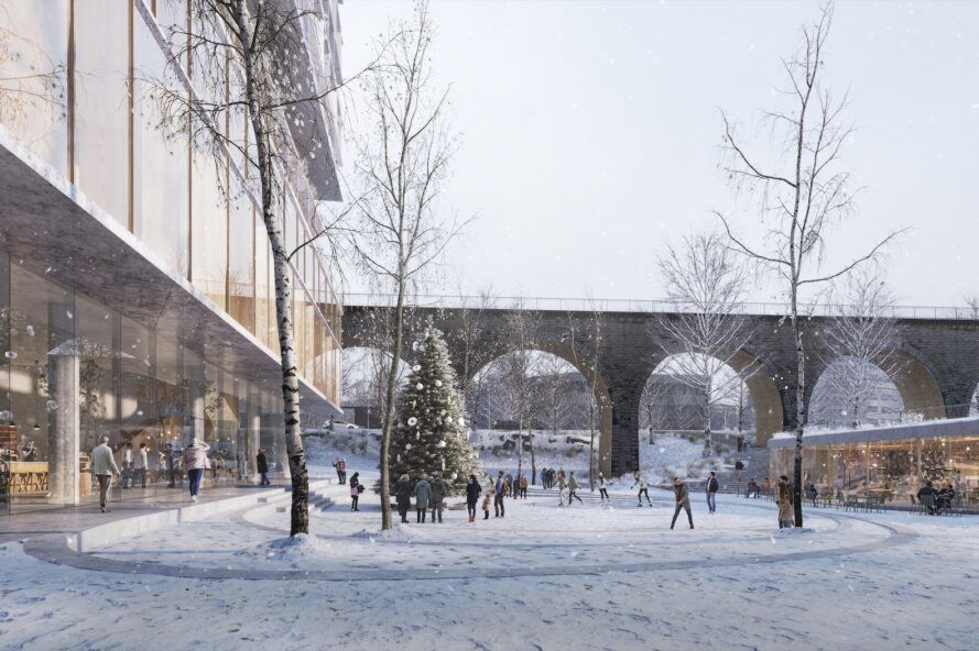 A winter landscape near a building with a connecting bridge with archways for people to walk through.