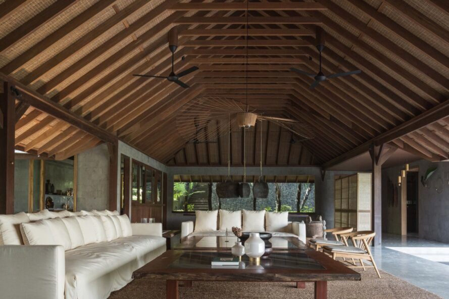 two large white sofas under pitched wood roof