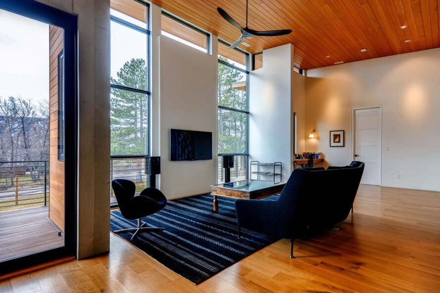 A living room area with a large dark blue sofa, a dark blue chair, wood floors and wood ceiling.