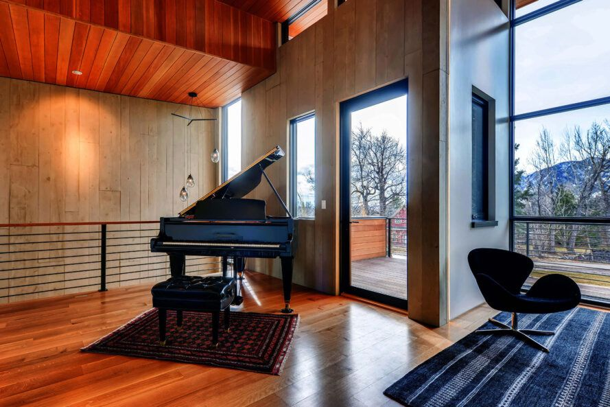 A large piano in the corner off the side of the living room.