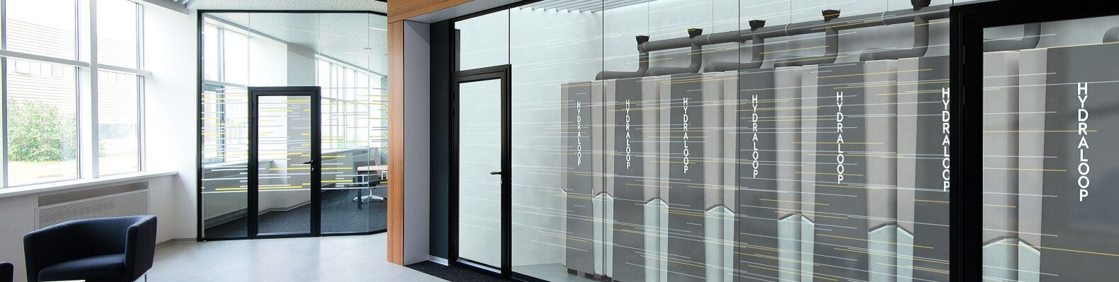 Glass door in an office revealing row of gray water recycling machines