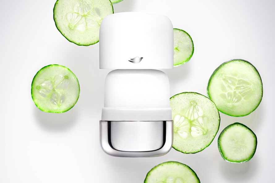 plastic and stainless steel deodorant tube with fresh cucumber slices on a white background