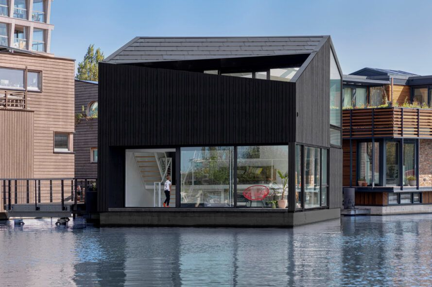 black timber floating home with glass walls on the first floor