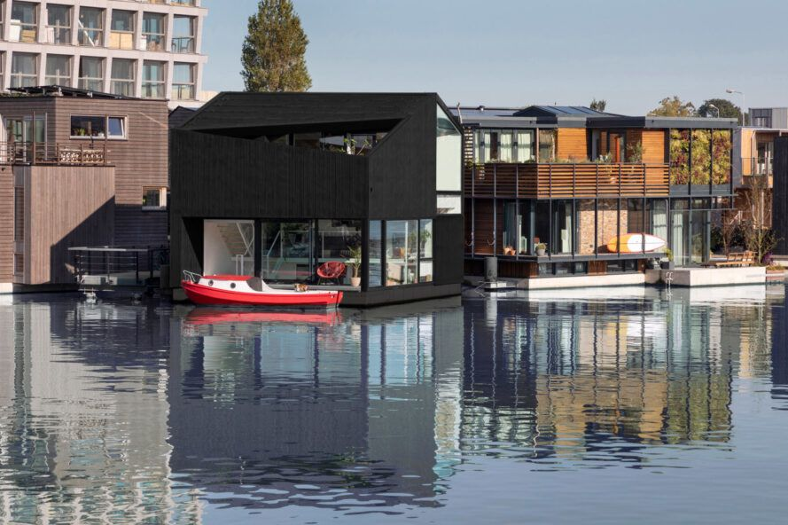 black home floating on a canal