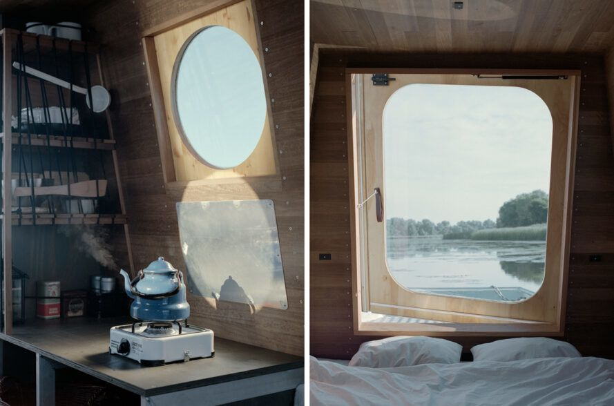On the left, kettle on a hot plate. On the right, small white bed near large window with lake views