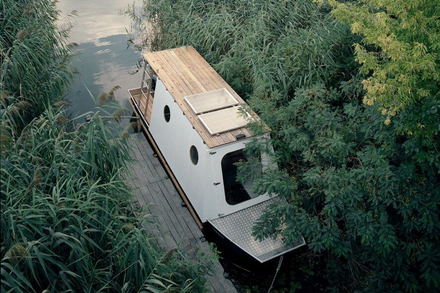 aerial view of timber and aluminum houseboat with solar panels on the roof