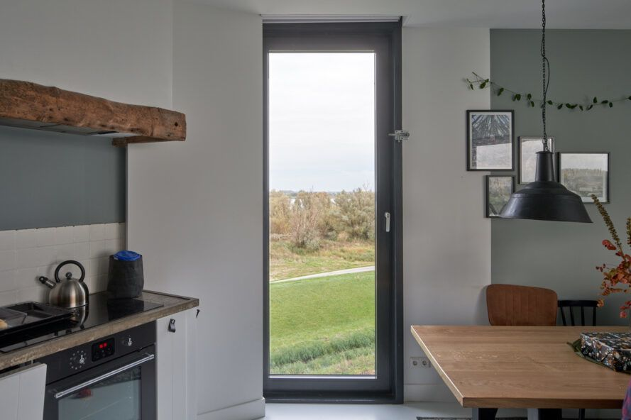 kitchen with tall, narrow window overlooking a polder landscape