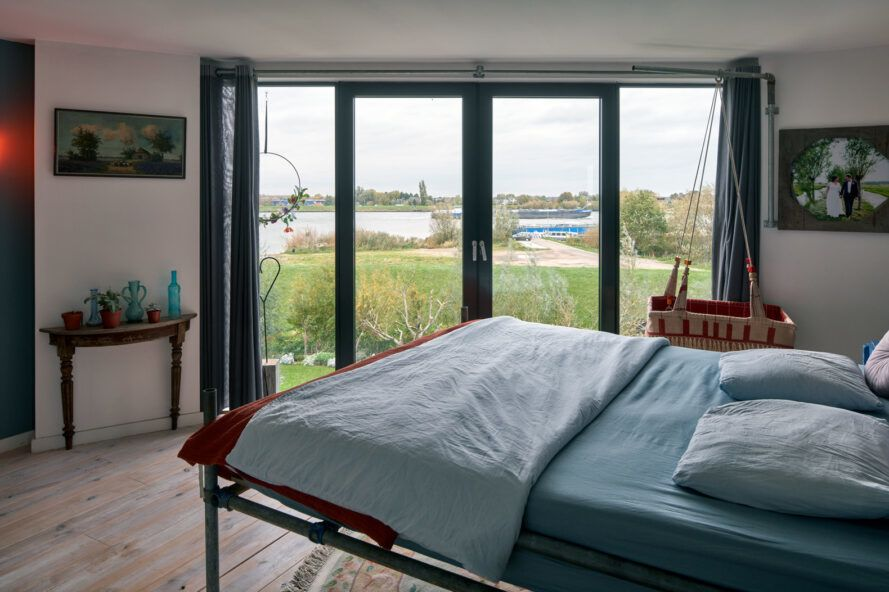 large blue bed facing a wall of glass