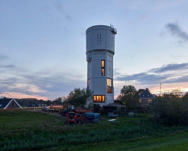 water tower with large windows lit up at dusk