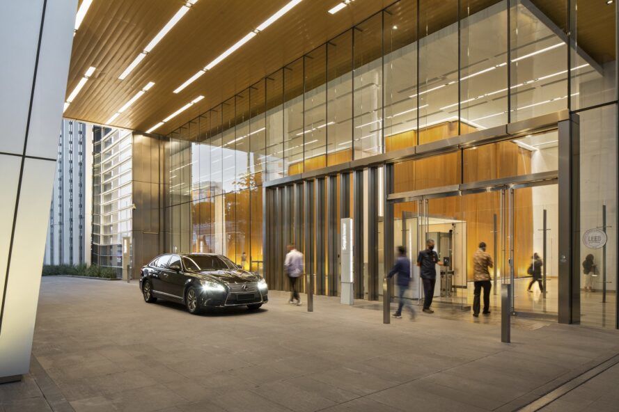 A car parked by the entrance to a large building with a glass facade.