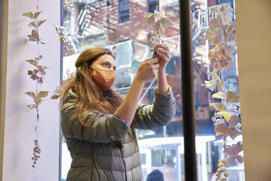 Artist Kim Markel wearing a face mask and working on an art display.