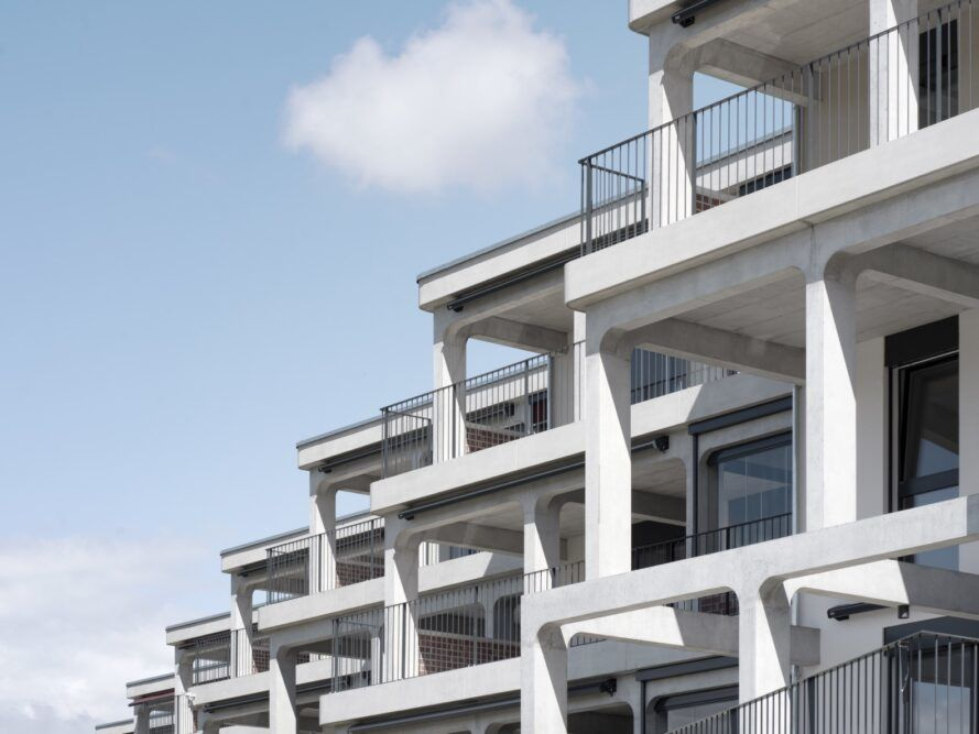 A housing complex with a tiered, off-white facade with balconies.
