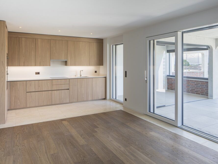 The interior of an empty apartment unit with light-colored wood accents and white paint.