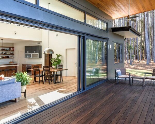 A dark-colored wood deck next to open sliding glass doors that lead inside the home.
