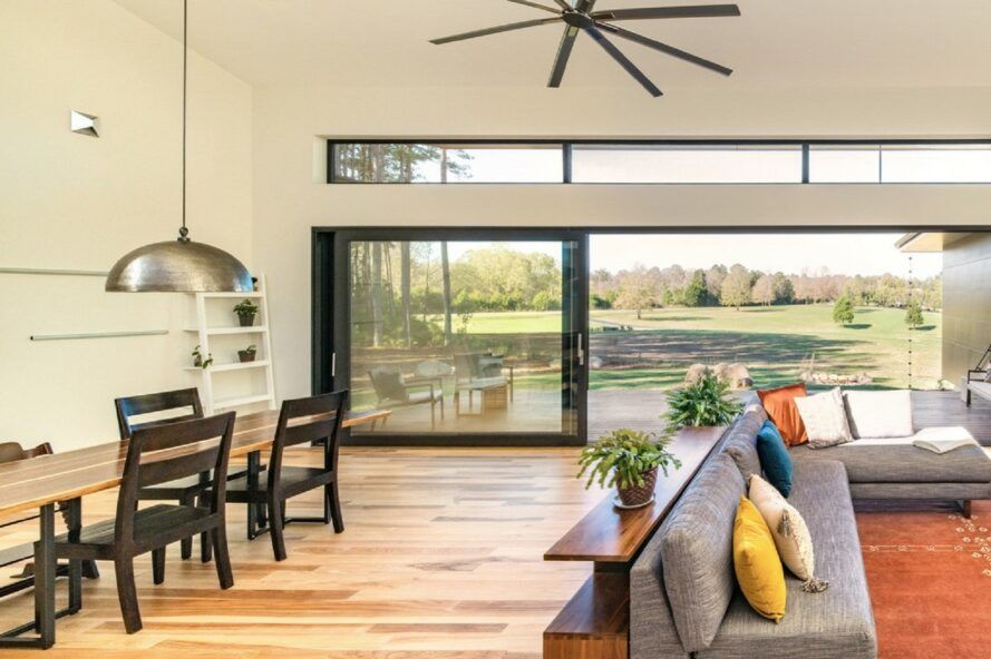 A living room with light-colored wood floors, a dining table with black chairs on the left and a sitting area with gray sofas and an orange rug on the right. The wall at the back of the room is a large sliding glass door that looks out on a green backyard.