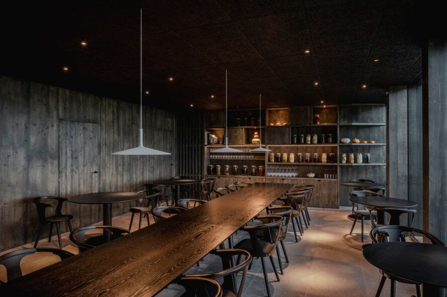 dark restaurant interior with dark wood tables and chairs