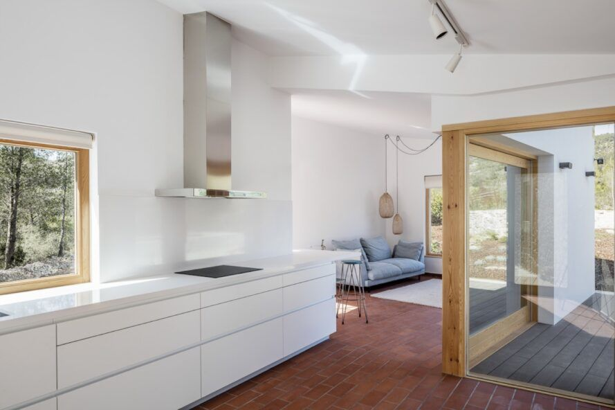 modern interior with all-white kitchen and a gray sofa just past the kitchen