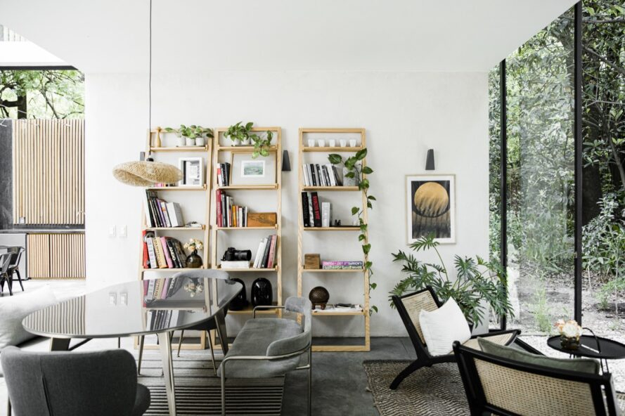 glass dining table near raw wood bookstands against the wall