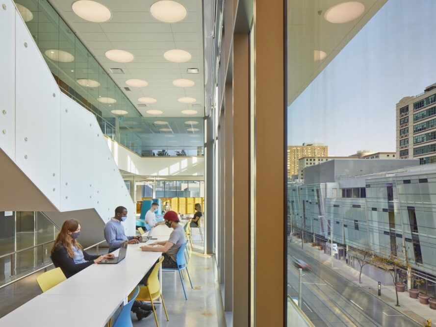 students sitting at long white table near a glass wall
