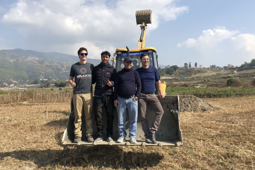 Four people stood on the tractor's shovel.