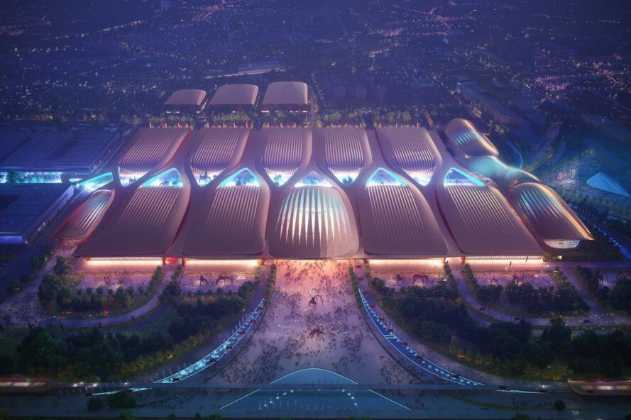 A bird's-eye view of a futuristic-looking building lit up in purple and blue with wishbone-shaped structures on the roof.