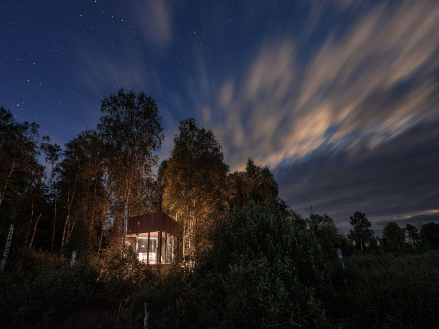 wood and glass cabin lit from within at dusk
