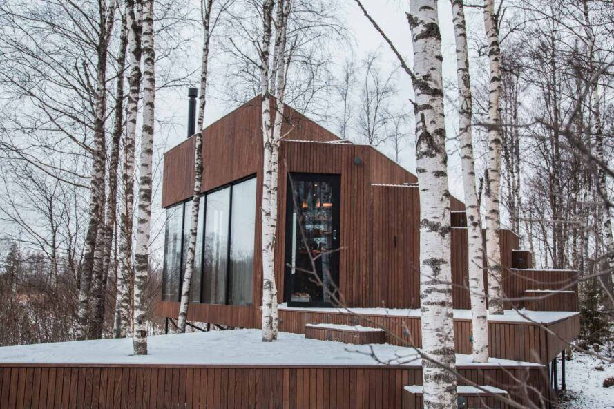 glass and wood cabin in snowy forest