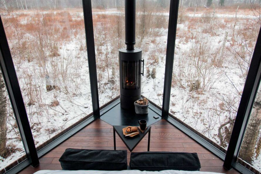 small sofa and table in front of fireplace and two glass walls