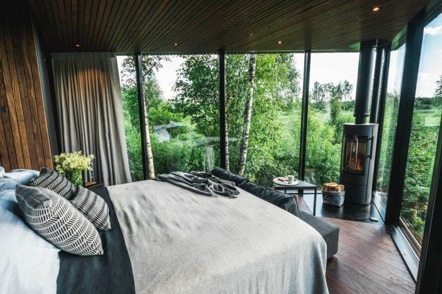 bed facing glass walls with forest views
