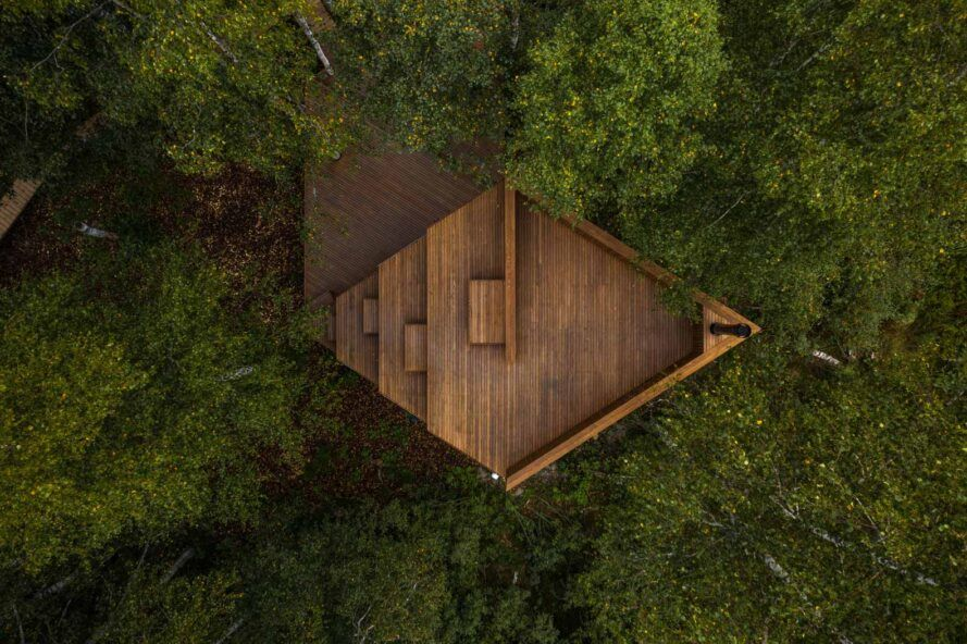 aerial view of diamond-shaped wood cabin in a forest