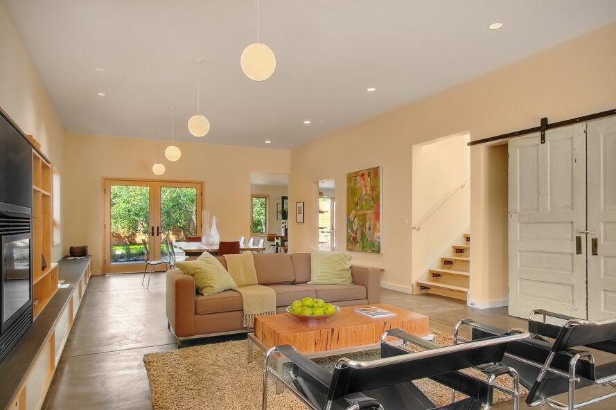 A living room with round hanging ceiling lights, a sofa, chairs and coffee table.