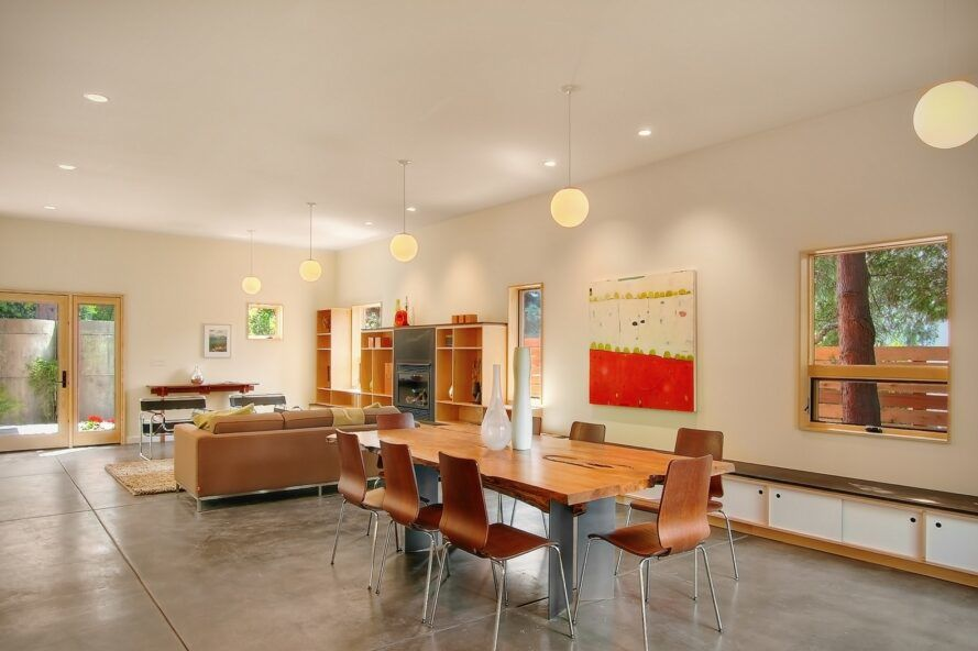 A dining roon with a wood rectangular table and several chairs surrounding it.