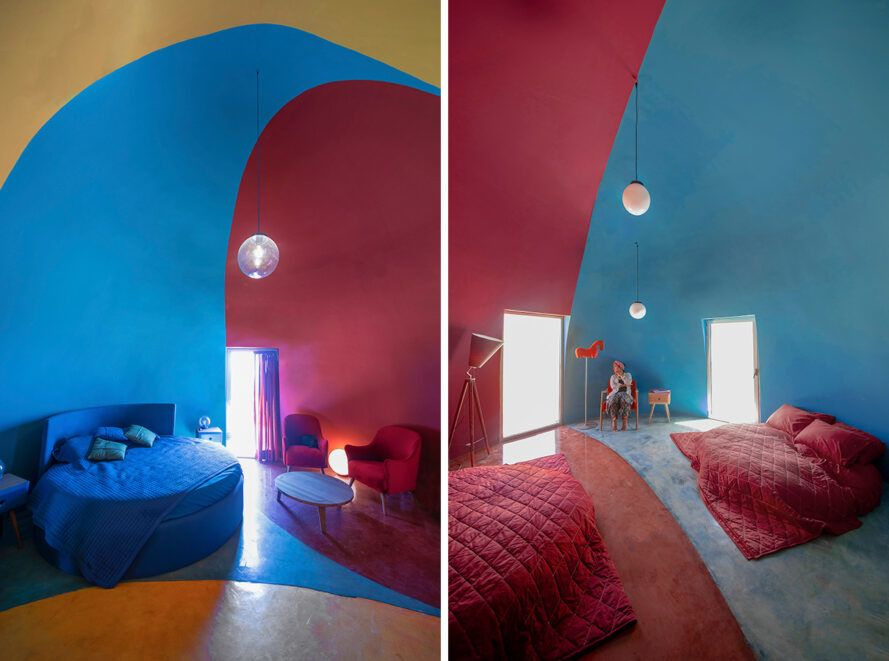 red, blue and yellow dome interior with blue sofa and red beds