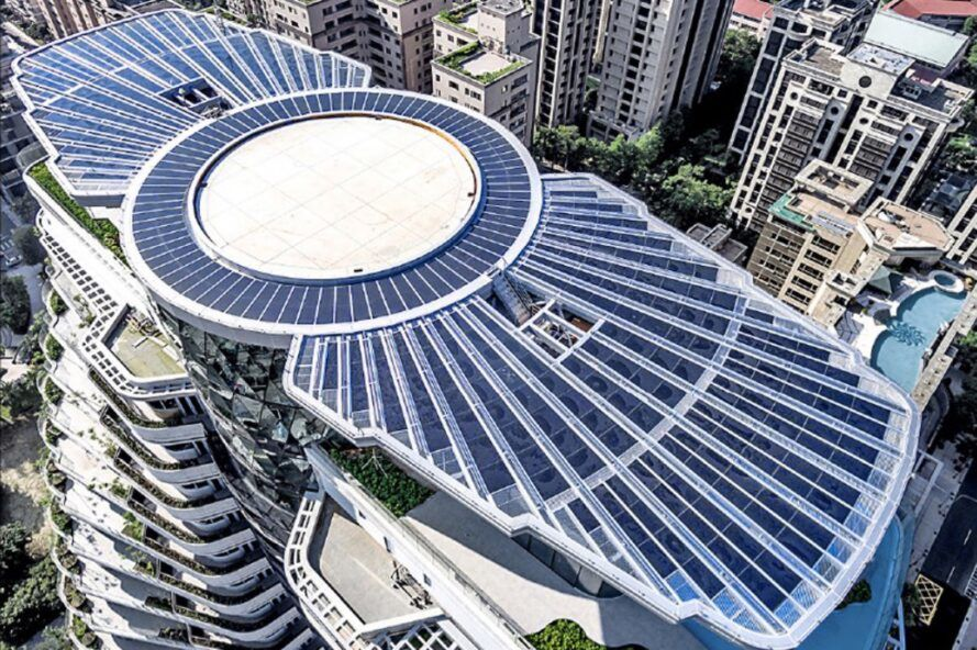 A bird's-eye view of the top of a skyscraper where a large white circle is flanked on either side by rooftop solar panels.