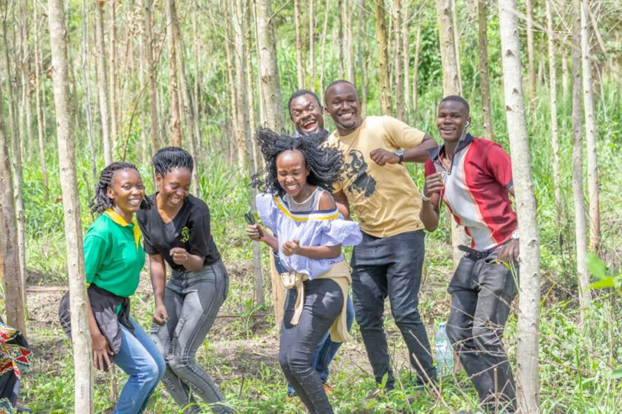 A group of six young people are dancing in a forest.