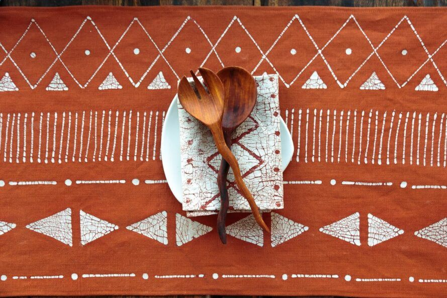 A set of wood spoons on top of an orange and white patterned cloth.