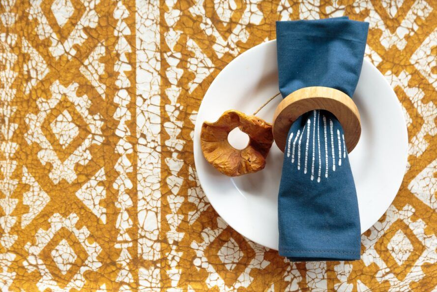 A napkin and napkin ring set on top of a white plate on an orange and white patterned cloth.