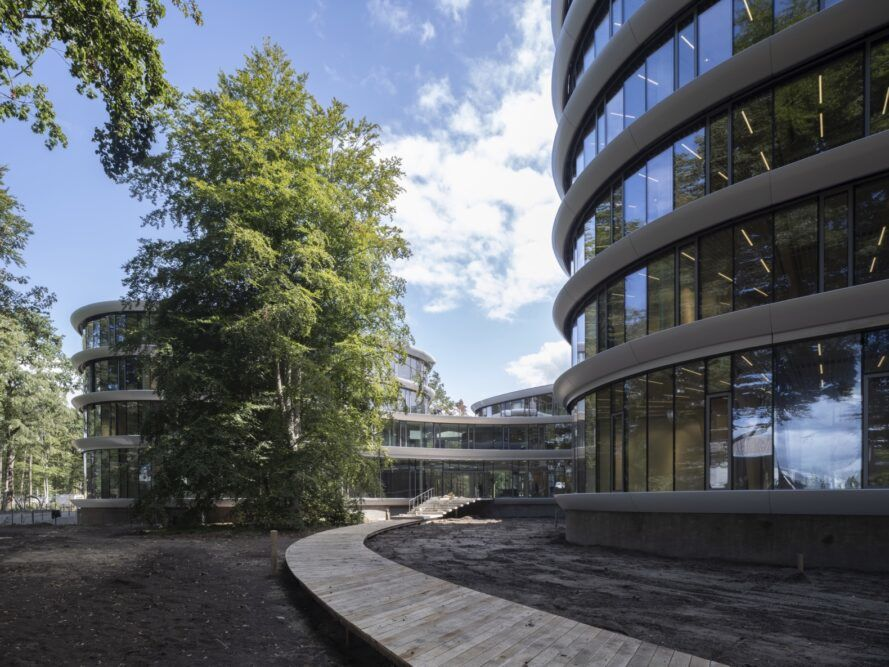 walkway around curving glass office building