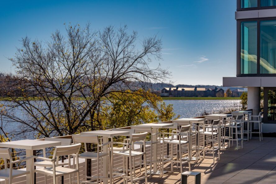 series of high-top tables and chairs on roof facing a river view