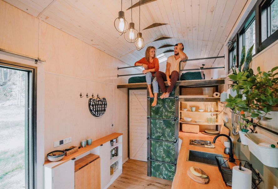 two people sitting on loft above a kitchen