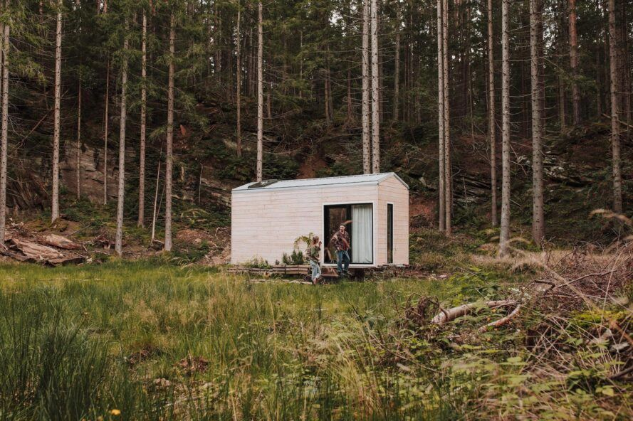 Couple sitting on front porch of wooden tiny home