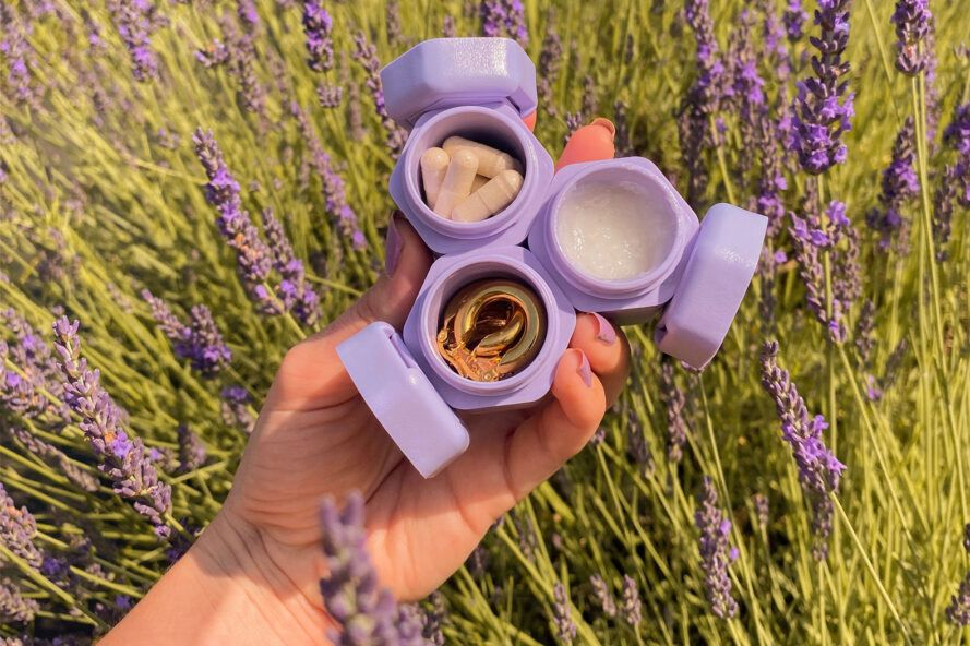 person holding travel capsules up against field of lavender
