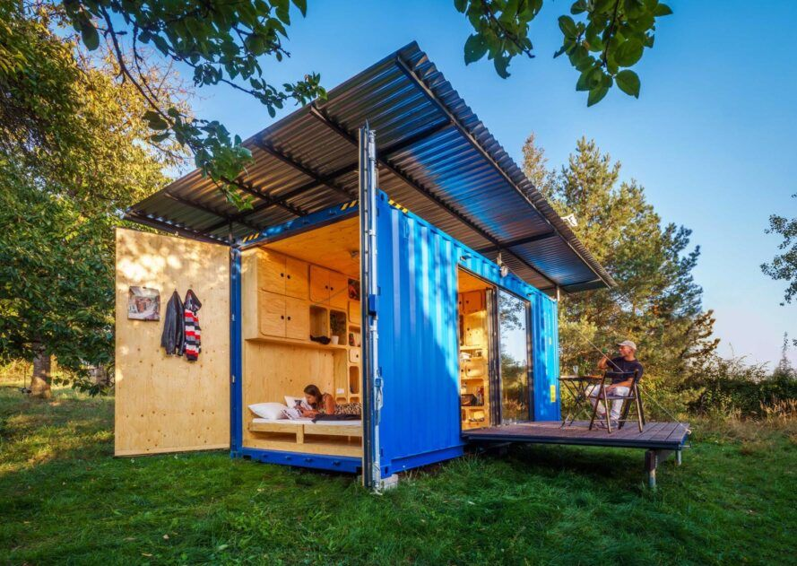 blue shipping container home with end wall open up