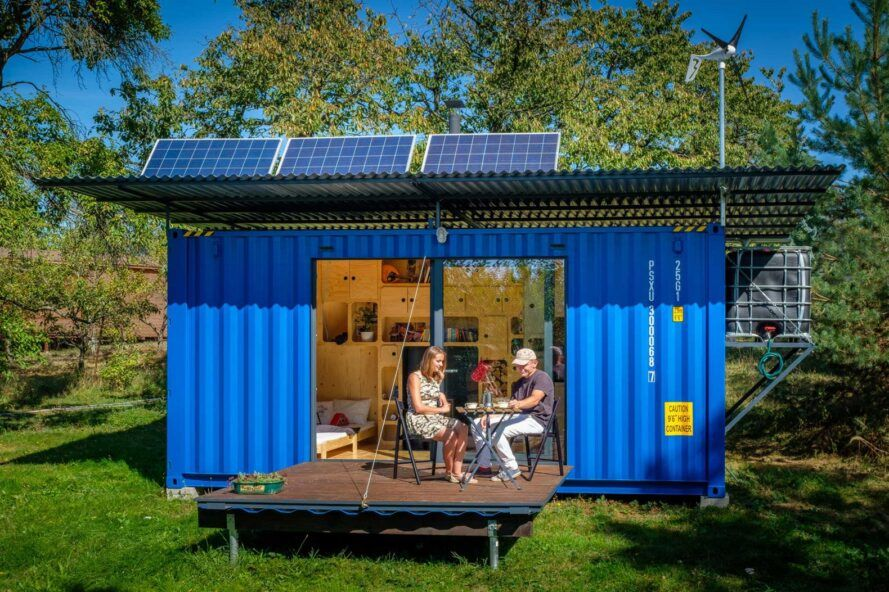 people sitting on patio connected to blue tiny home